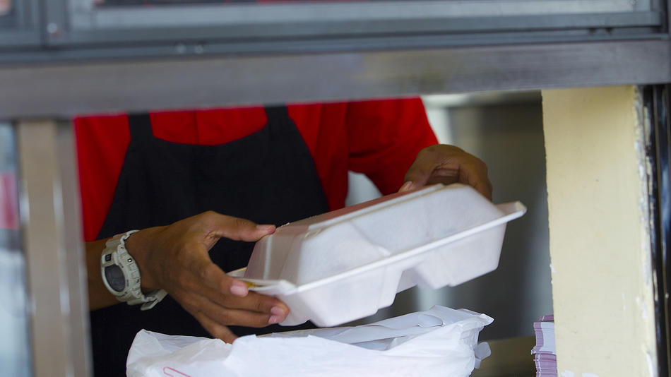 styrofoam to-go container in hand