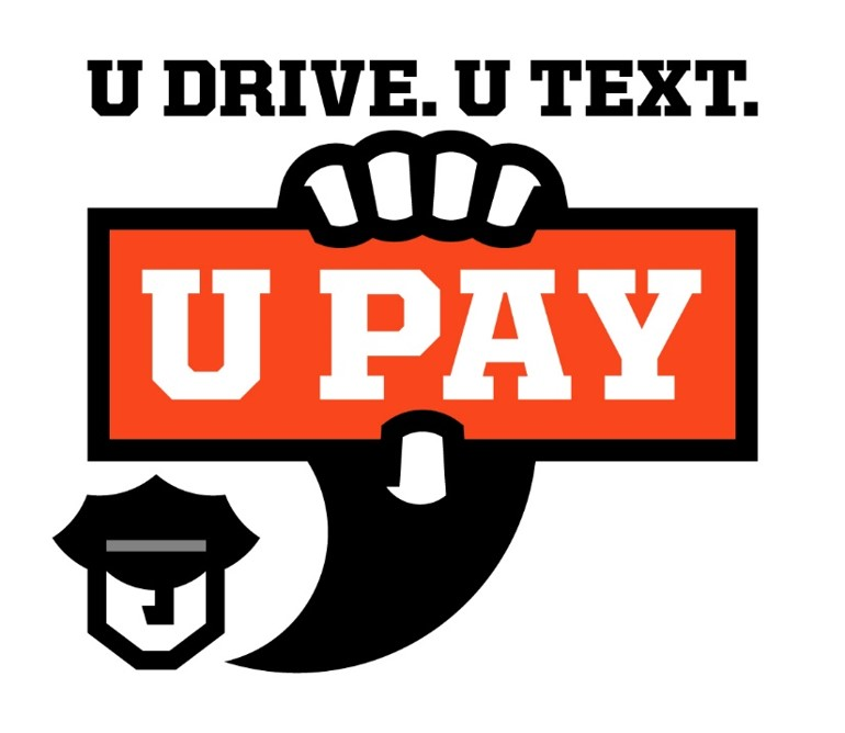 "Police officer holding a sign that says ""U Pay"" if you text and drive."