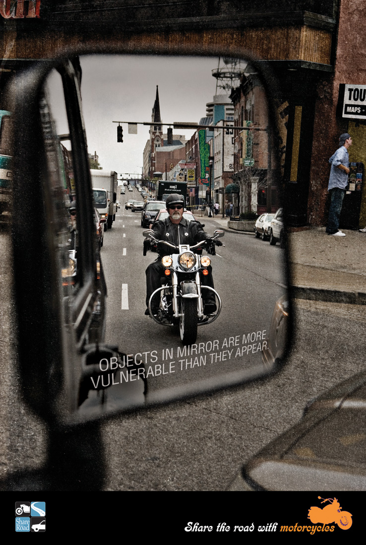 "Motorcyclist reflected in a side mirror of a car. Text says ""Objects may be more vulnerable than they appear."""