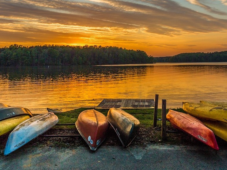 Kayaks and canoes sit at shoreline of Lake Brandt at Sunset