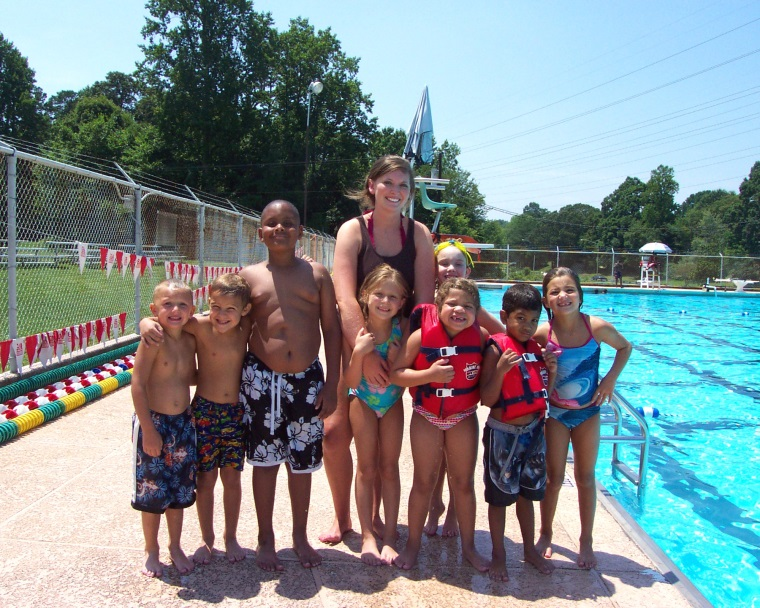 Children and swim coach standing at pool and smiling
